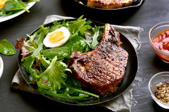 Fried pork steak with green salad. Close up view stock image