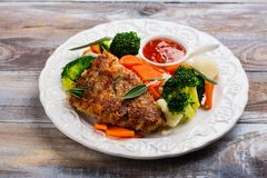 Fried pork steak with vegetables garnish. Copy space Stock Photo