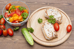 Fried pork steak with vegetables and parsley on a wooden board Stock Image
