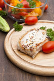 Fried pork steak with vegetables and parsley on a wooden board Royalty Free Stock Photo