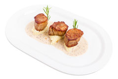 Fried pork tenderloin medallions on mashed potatoes. Royalty Free Stock Images