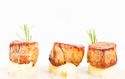 Fried pork tenderloin medallions on mashed potatoes. Stock Photo