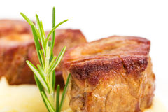 Fried pork tenderloin medallions on mashed potatoes. Royalty Free Stock Photography