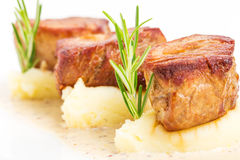 Fried pork tenderloin medallions on mashed potatoes. Royalty Free Stock Image