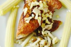 Fried pork topping garlic with boiled baby corn and Buna shimeji mushroom on plate Stock Photo