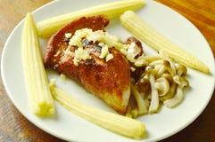 Fried pork topping garlic with boiled baby corn and Buna shimeji mushroom on plate Stock Photography
