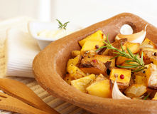 Fried potato. Photo of tasty fried potato with garlic, baked vegetables, french fries with grilled vegetable in wooden plate on the table, healthy food, organic stock photography