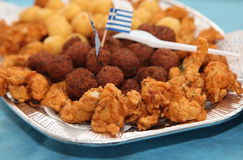 Fried potato balls and meat balls with schnitzel. With Greece flag on a silver plate stock photography