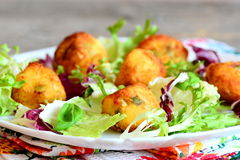Fried potato balls with salad leaf mix and basil on a plate. Small golden fried balls made from mashed potatoes stock photo