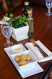 Fried potato balls with sauce on served restaurant table. Dish of fried potato balls on wooden table with cutlery,napkin and empty wine glass royalty free stock photography