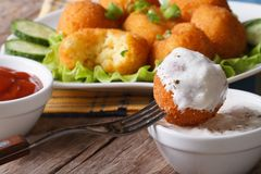 Fried potato balls with sour cream close-up horizontal. Royalty Free Stock Photo
