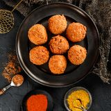 Fried potato cheese balls or croquettes with spices on black plate over dark stone background stock images