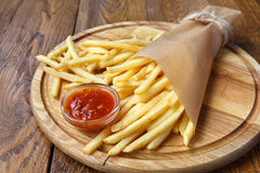 Fried potato chips wrapped takeaway on wood Royalty Free Stock Photo