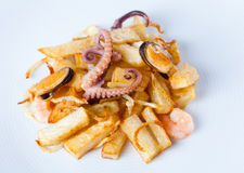 Fried potato cuttlefish octopus mussels shrimp. White plate background up view. Fried potato cuttlefish octopus mussels shrimp. White plate background, up view Royalty Free Stock Images
