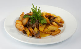 Fried potato with mushrooms. Fried potato with mushrooms and greens Stock Photography