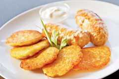 Fried potato pancakes with chicken sausages Royalty Free Stock Photography