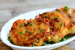 Fried potato pancakes or draniki with ham slices and green onion on a white plate. Simple draniki recipe. Closeup stock image