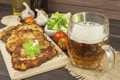 Fried potato pancakes with garlic. Traditional Czech food. Preparing homemade food. Potato pancakes and beer glasses royalty free stock photography
