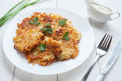 Fried potato pancakes or latke traditional. Homemade Hanukkah celebration food with greens and sour cream sauce recipe in plate on rustic white wooden table Royalty Free Stock Photography