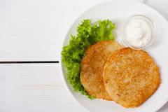 Fried potato pancakes with sour cream and fresh leaf salad on a white plate Royalty Free Stock Images