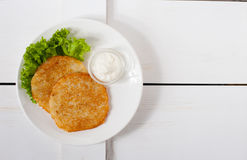 Fried potato pancakes with sour cream and fresh leaf salad on a white plate Royalty Free Stock Photo