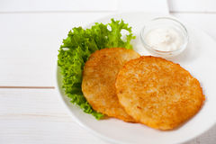 Fried potato pancakes with sour cream and fresh leaf salad on a white plate Royalty Free Stock Image
