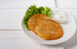 Fried potato pancakes with sour cream and fresh leaf salad on a white plate Stock Photo