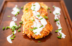 Fried potato pancakes with sour cream and green onions Stock Image
