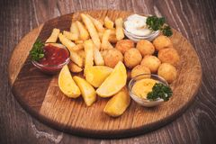 Fried potato platter with dips Stock Images