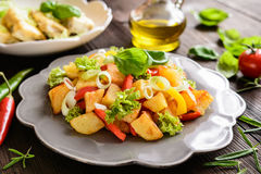 Fried potato salad with lettuce, pepper, onion and baked fish fi Stock Photo