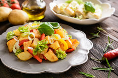 Fried potato salad with lettuce, pepper, onion and baked fish fi Royalty Free Stock Photography