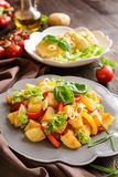 Fried potato salad with lettuce, pepper, onion and baked fish fi Royalty Free Stock Image