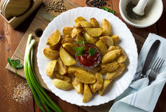 Fried potato slices. A composition of fried potatoes, sauce and parsley Royalty Free Stock Photography