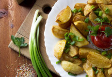 Fried potato slices. A composition of fried potatoes, sauce and parsley Royalty Free Stock Images