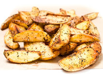 Fried potato wedges country styled with herbs and spices on perc Royalty Free Stock Photography