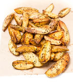 Fried potato wedges country styled  on  kraft paper. Fast food. Stock Image