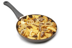 Fried potato wedges on the pan. Fried potato wedges with onion and mushrooms on the pan Stock Photo