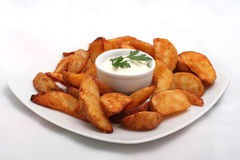 Fried potato wedges with white sauce on plate Royalty Free Stock Images