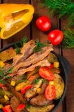 Fried potatoes with bacon and fresh tomatoes in the frying pan. Wooden rustic background. Top view stock images