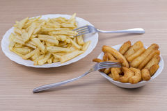 Fried potatoes and calamari. Royalty Free Stock Images