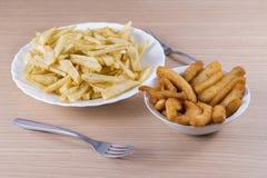Fried potatoes and calamari. Royalty Free Stock Photography