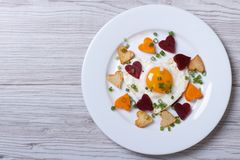Fried potatoes, carrots, beets and egg of heart on a plate. Royalty Free Stock Photos