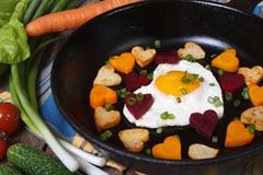 Fried potatoes, carrots, beets and egg in a heart shape Stock Photo