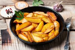 Fried potatoes in a cast iron pan royalty free stock images
