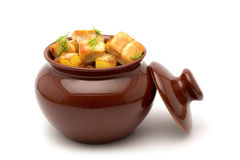 Fried potatoes with chunks of meat in a clay pot on a white back Stock Photography