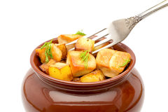 Fried potatoes with chunks of meat in a pot with a fork close up on a white background Royalty Free Stock Image