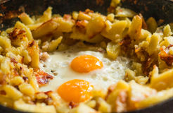 Fried potatoes with eggs in pan Stock Image