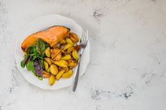 Fried potatoes with fish and green salad on a white plate Stock Photo
