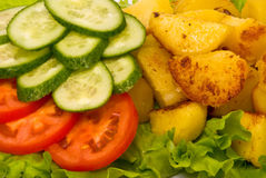 Fried potatoes with fresh cucumbers and tomatoes Stock Photo