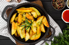 Fried potatoes with fresh rosemary in cast-iron pan, rustic styl Royalty Free Stock Photography